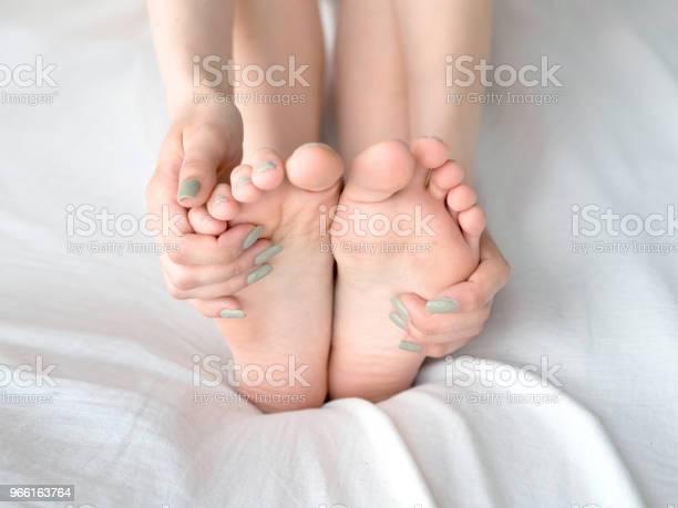 Ung Kvinna Massera Hennes Fot På Sängen Hälsooch Koncept-foton och fler bilder på Asiatiskt och indiskt ursprung