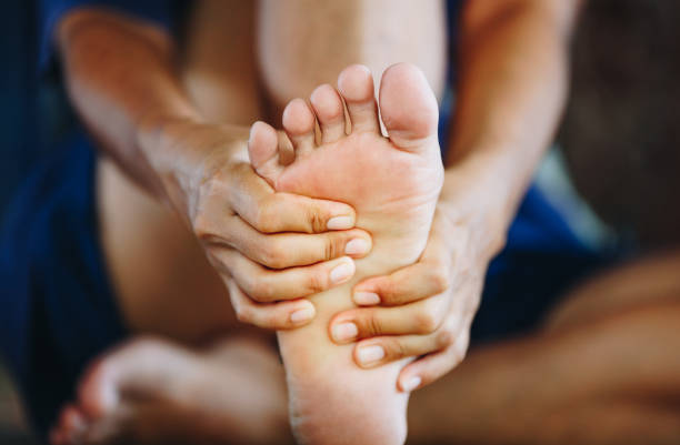 young woman massaging her painful foot , health care concept young woman massaging her painful foot , health care concept foot stock pictures, royalty-free photos & images