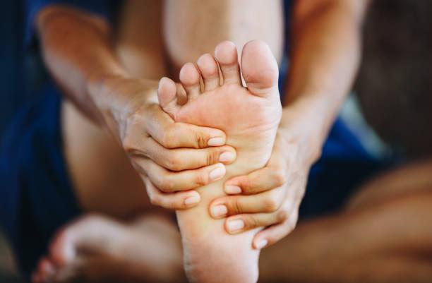 young woman massaging her painful foot , health care concept - stopa zdjęcia i obrazy z banku zdjęć