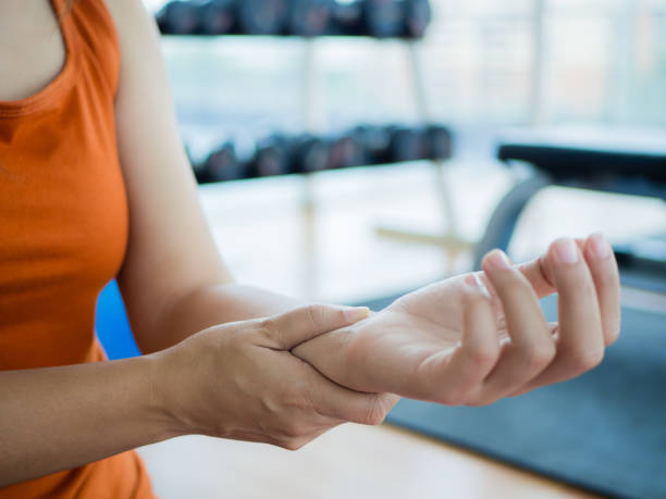 Young woman massaging her wrist after working out or injured hand during careless sport practice with fitness equipment background. stock photo