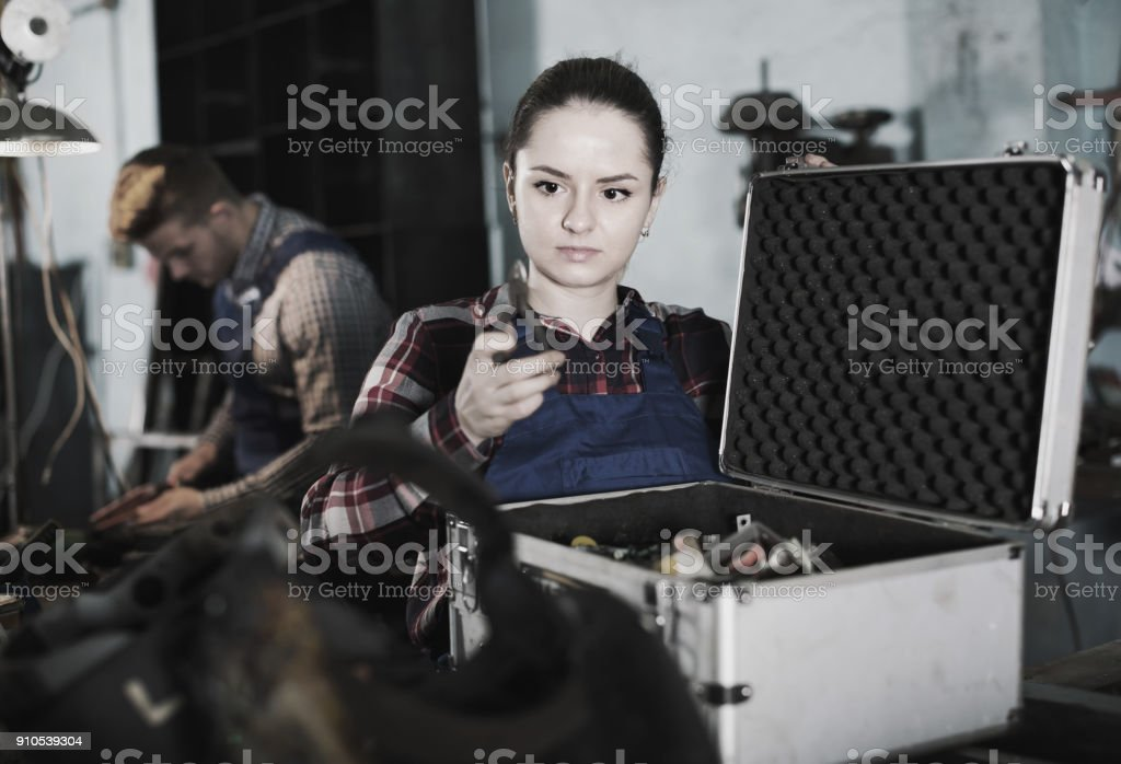 Young woman master is looking tools in box in workplace