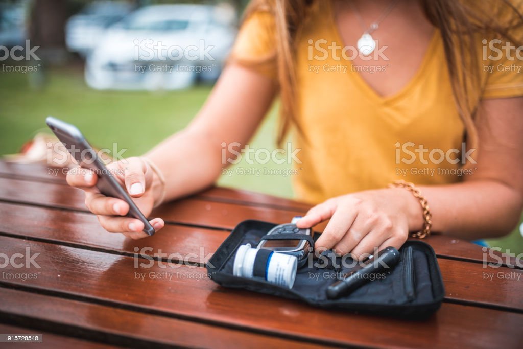 Young woman measuring blood sugar level and using mobile phone stock photo