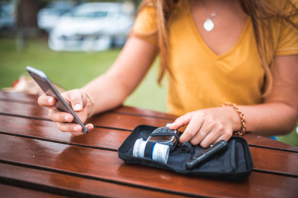 young woman measuring blood sugar level and using mobile phone - diabetic stock photos and pictures