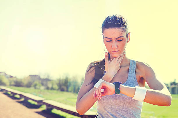 Young woman measuring heart rate after running stock photo