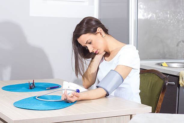 young woman measuring her blood pressure stock photo