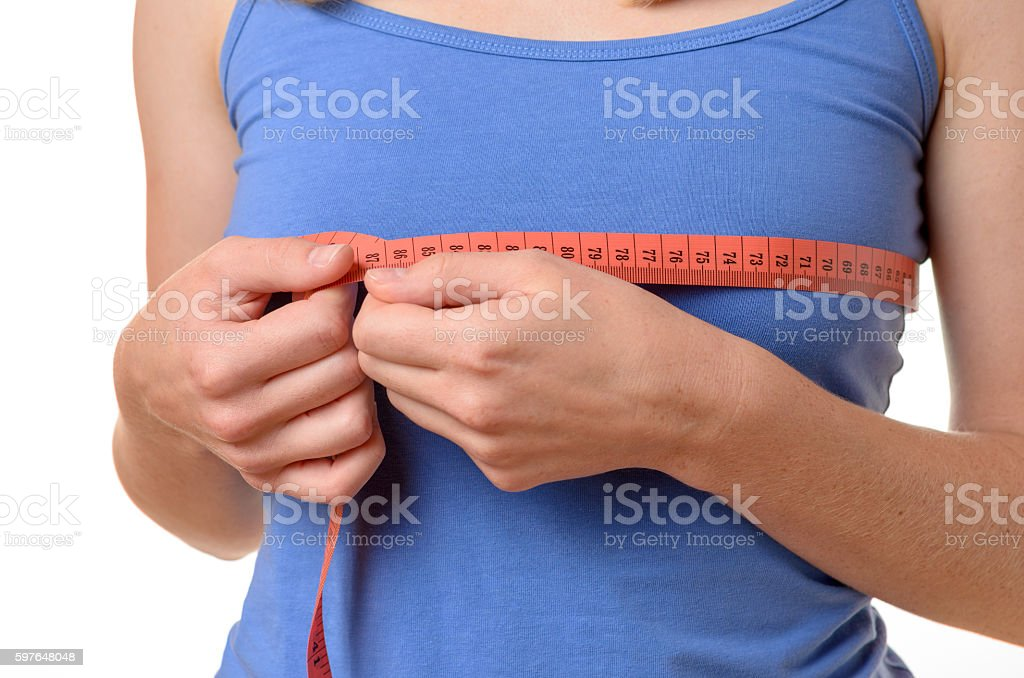 Young woman measuring her breasts stock photo