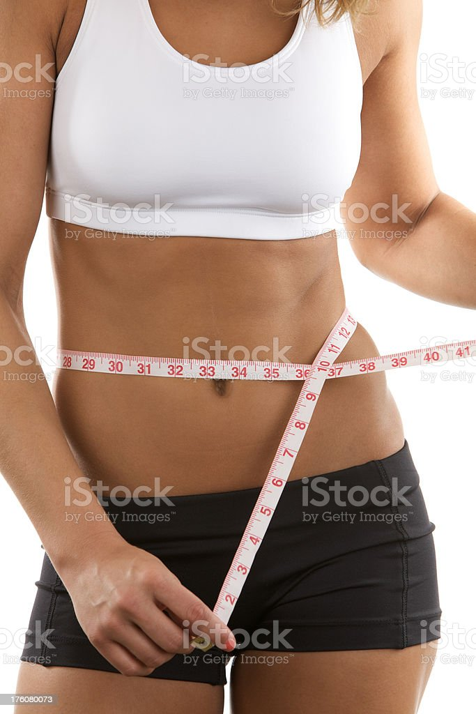 Young woman measuring her own waist royalty-free stock photo