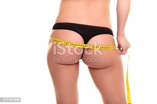 91837830istockphoto Young Woman measuring her waist - Stock Image 470761688
