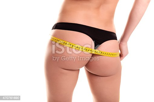 91837830istockphoto Young Woman measuring her waist - Stock Image 470761692