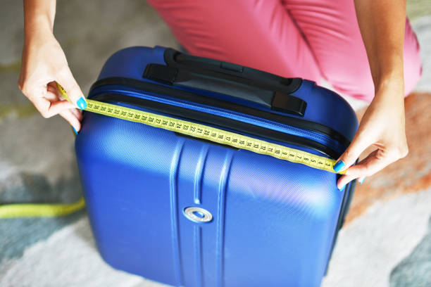 Young woman measuring travel luggage or suitcase before flight Young woman measuring travel luggage or suitcase before flight carry on luggage stock pictures, royalty-free photos & images