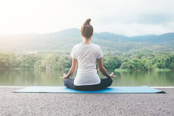 Young woman meditates while practicing yoga in park. Freedom concept. Calmness and relax, female happiness. blurred garden on the background stock photo