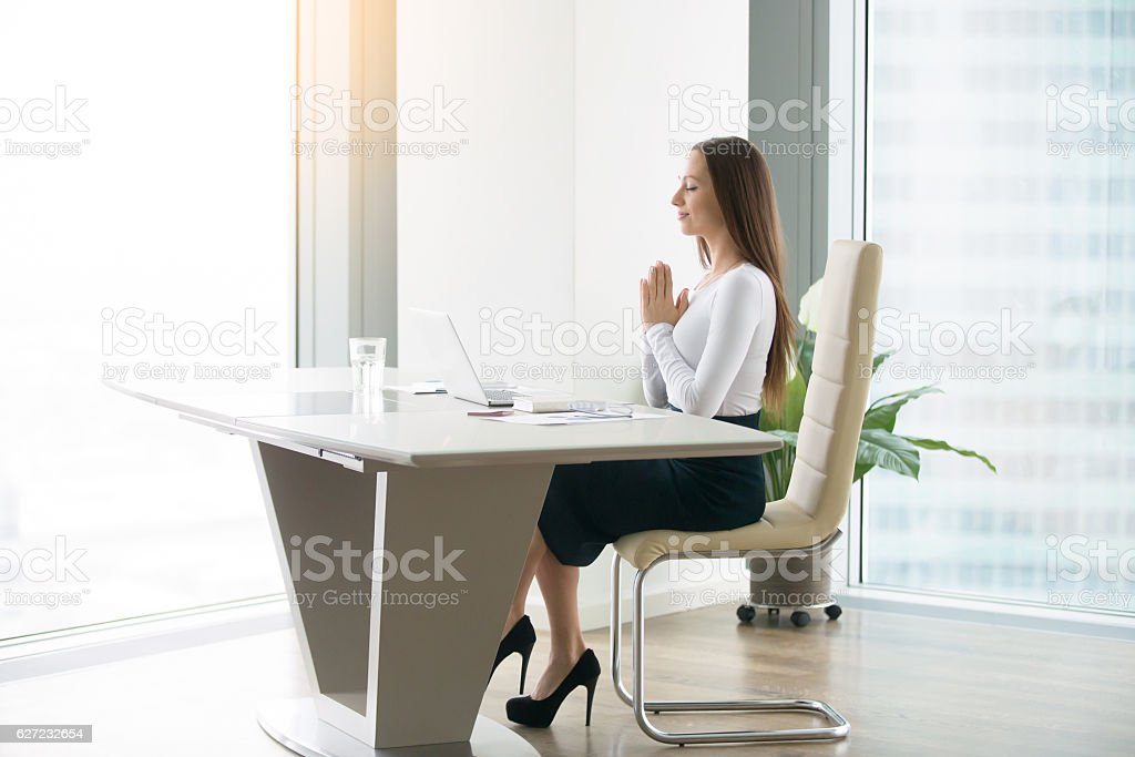 Young woman meditating at the office desk stock photo