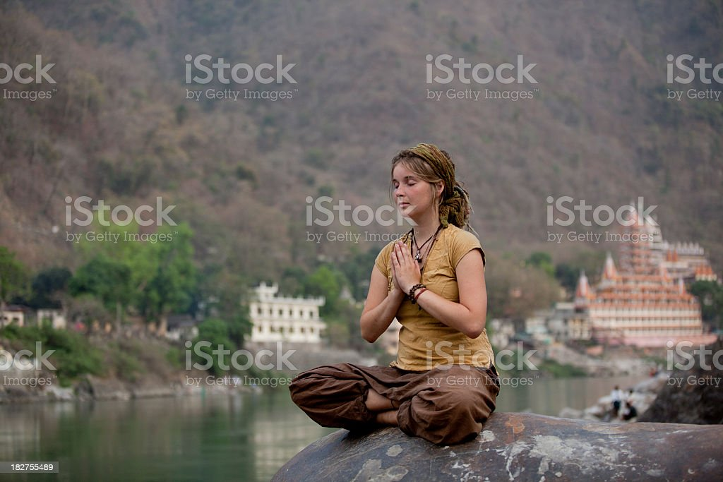 Young Woman Meditating By Ganges River In Rishikesh, India stock photo