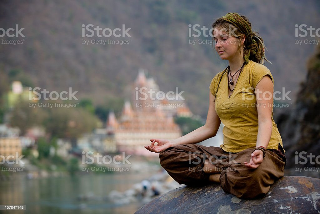 Young woman meditating by ganges river in rishikesh stock photo
