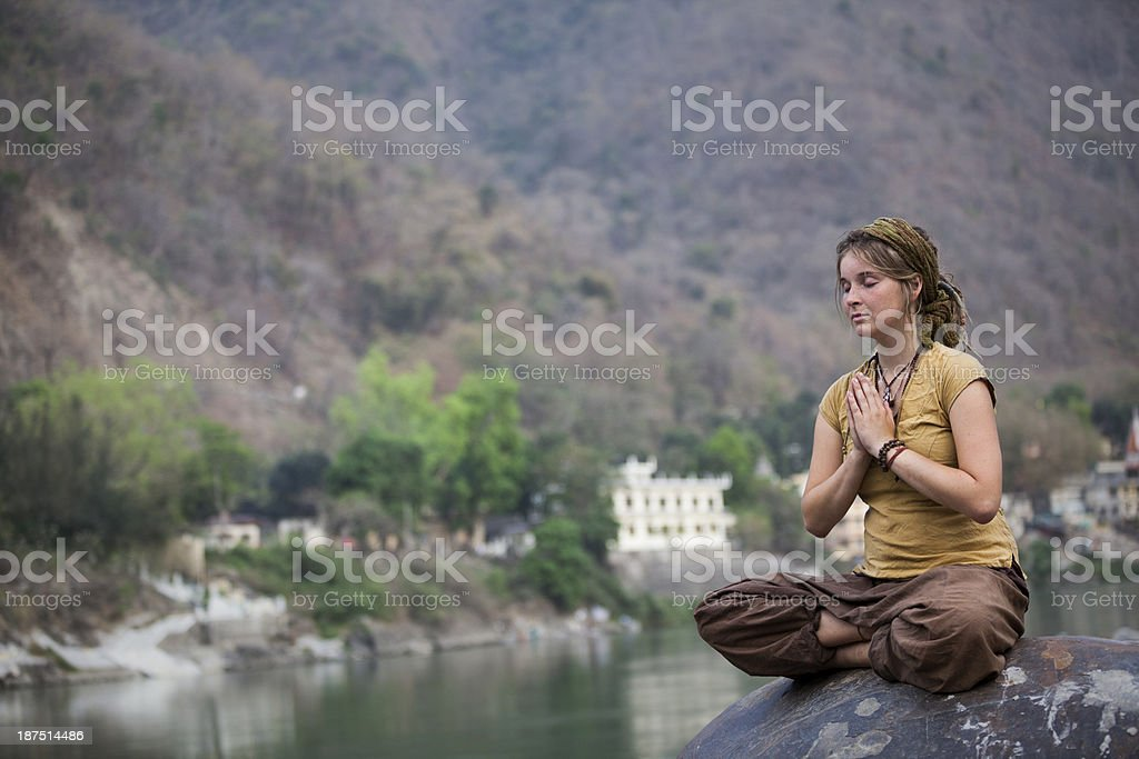 Young woman meditating by ganges river in rishikesh Young woman meditating by ganges river in Rishikesh, India Adult Stock Photo