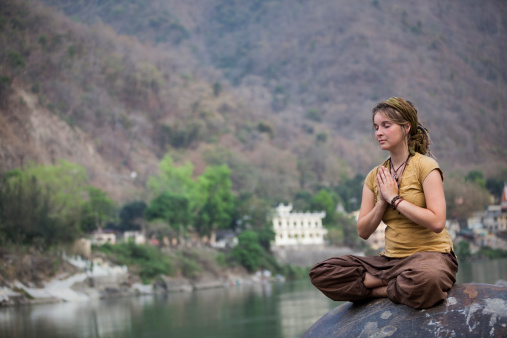 Young Woman Meditating By Ganges River In Rishikesh Stock Photo - Download Image Now
