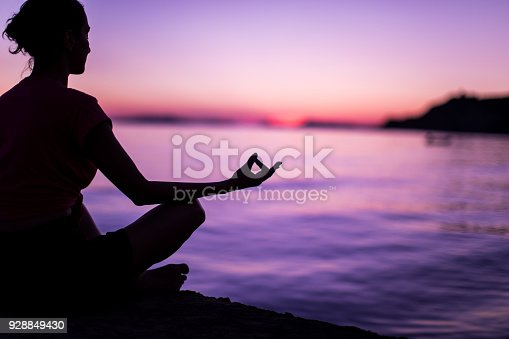 Calm Mindful Woman Meditating On Beach Faced Towards Majestic Sunset
