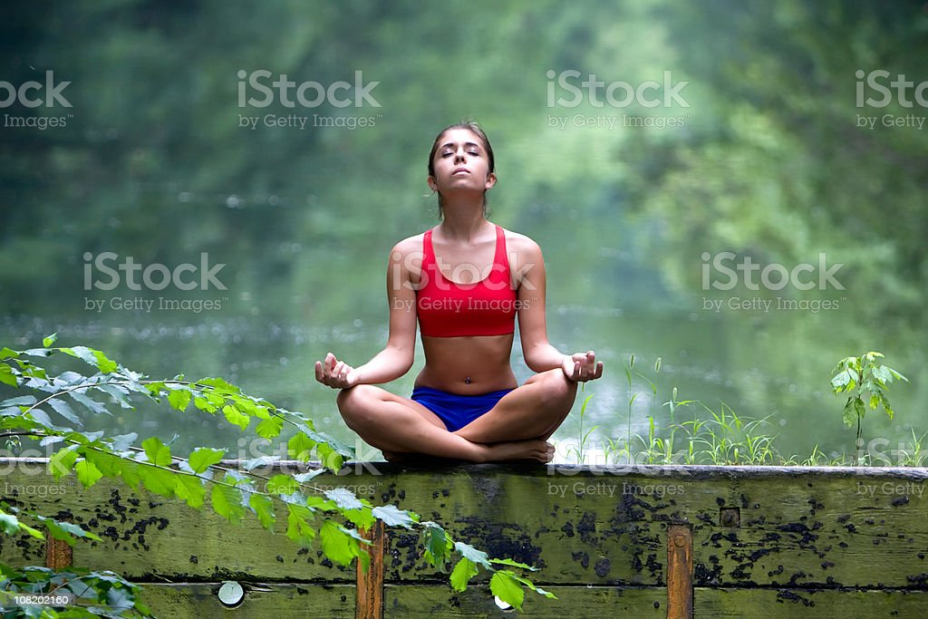 Young Woman Meditating in Forest royalty-free stock photo