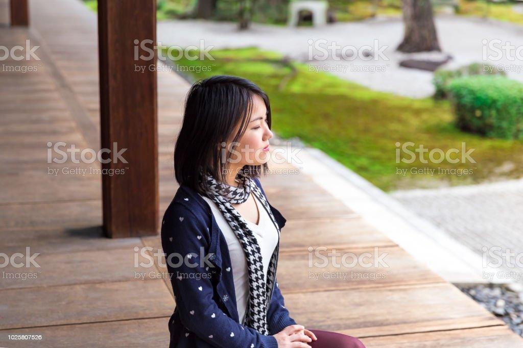 若い女性の寺院で日本の石庭の前で瞑想 ストックフォト