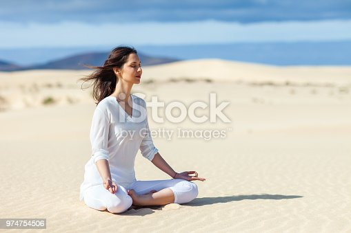 istock Young woman meditating in Lotus Pose in desert on Canary Islands, Spain. 974754506
