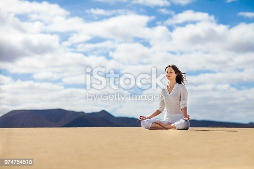 istock Young woman meditating in Lotus Pose in desert on Canary Islands, Spain. 974754510