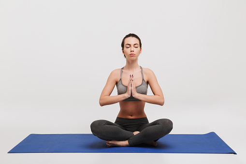 young woman meditating in lotus pose on yoga mat isolated on white