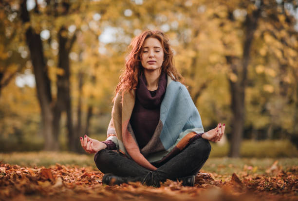 Young woman meditating in Lotus position at the park. Ginger woman doing Yoga breathing exercises with her eyes closed during autumn day. lotus position stock pictures, royalty-free photos & images