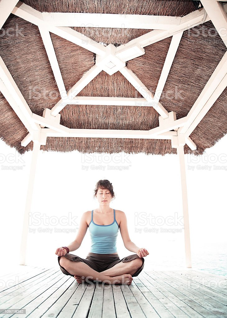 Young Woman Meditating in Lotus Position on Beach Deck royalty-free stock photo