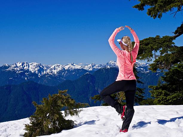 Young Woman Meditating in Mountains. stock photo