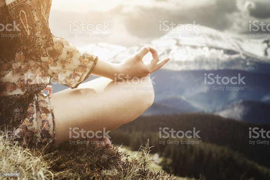 Young woman meditating in the mountains stock photo