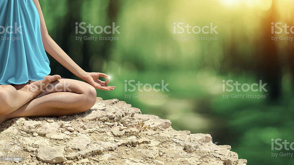 Young woman meditating in the spring forest stock photo