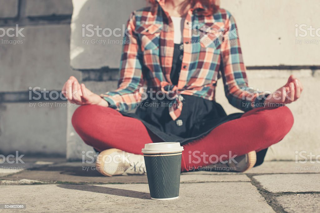 Young woman meditating in the street stock photo