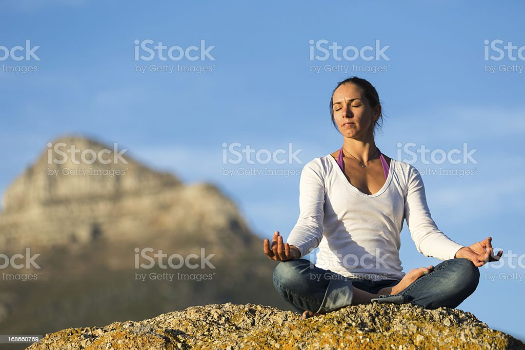 Young Woman Meditating on a Rock stock photo