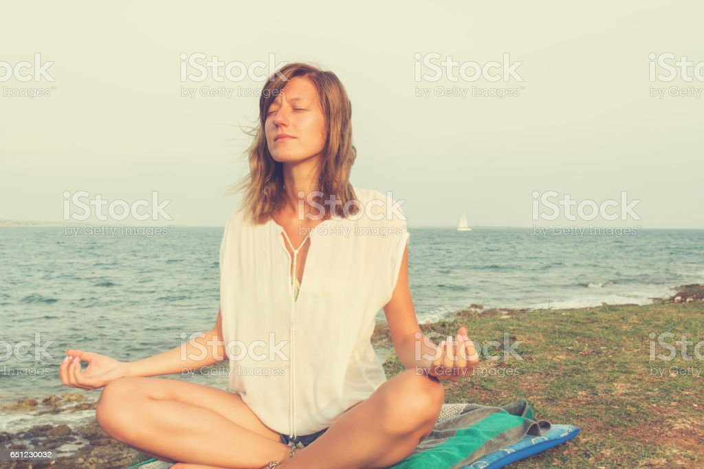Young woman meditating on a sea shore. stock photo
