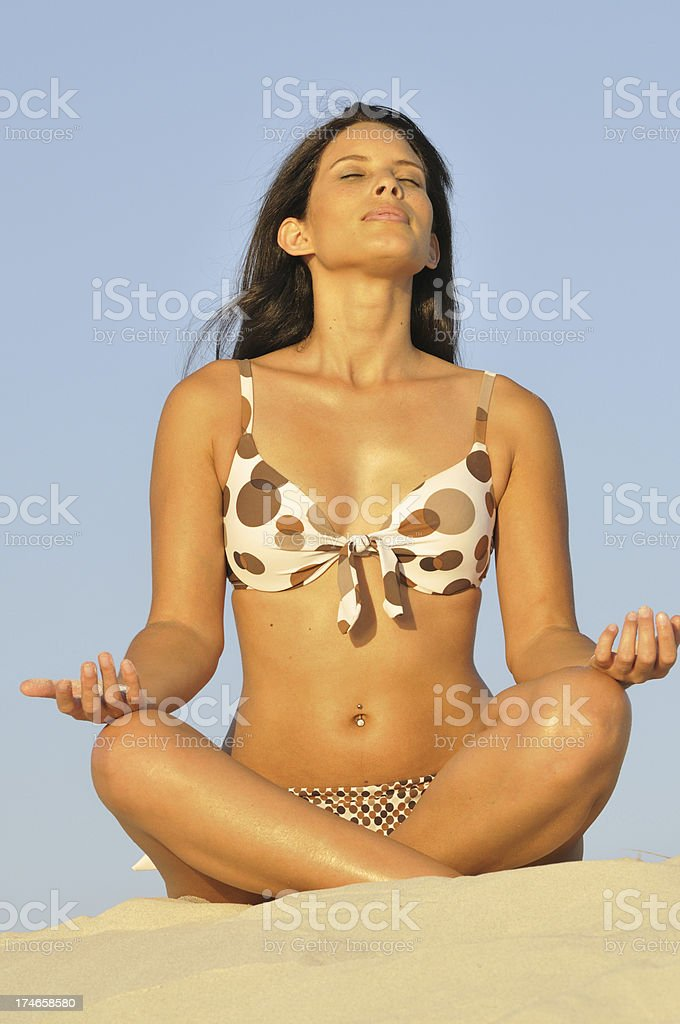 Young woman meditating on beach stock photo