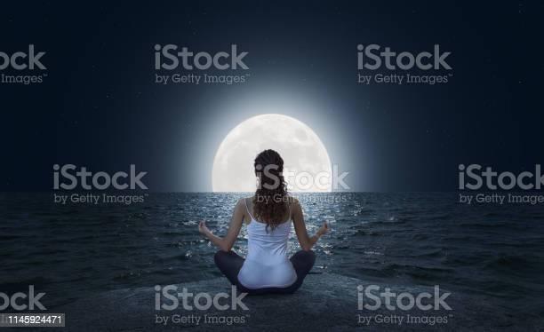 Junge Frau Meditiert Am Strand Bei Vollmond Stockfoto und