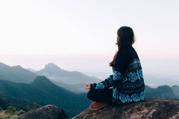 mulher nova que meditando sobre a montanha - meditation - fotografias e filmes do acervo