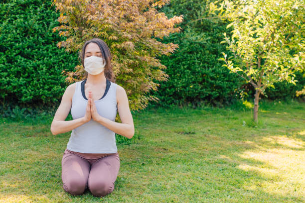 Young woman meditating outdoors in a park or garden with surgical facemask - concept of making yoga and fitness exercises during or after coronavirus outbreak