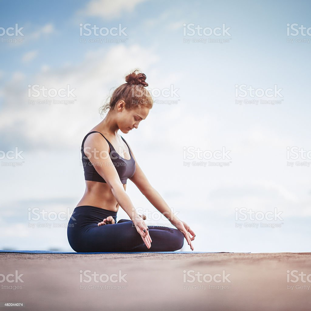 Young woman meditating outdoors on a rooftop stock photo