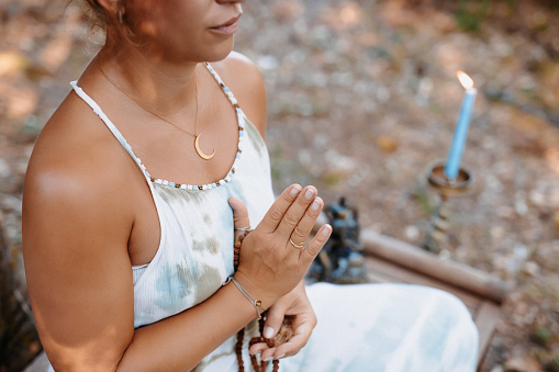 Meditating young woman sitting on a wooden bench, selective focus and  grain added, part of a series