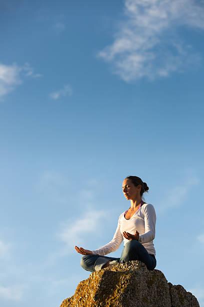 Young Woman Meditating While Facing the Sun stock photo