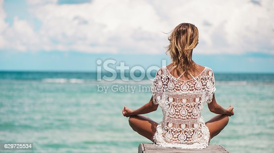 istock young woman meditation at the beach 629725534