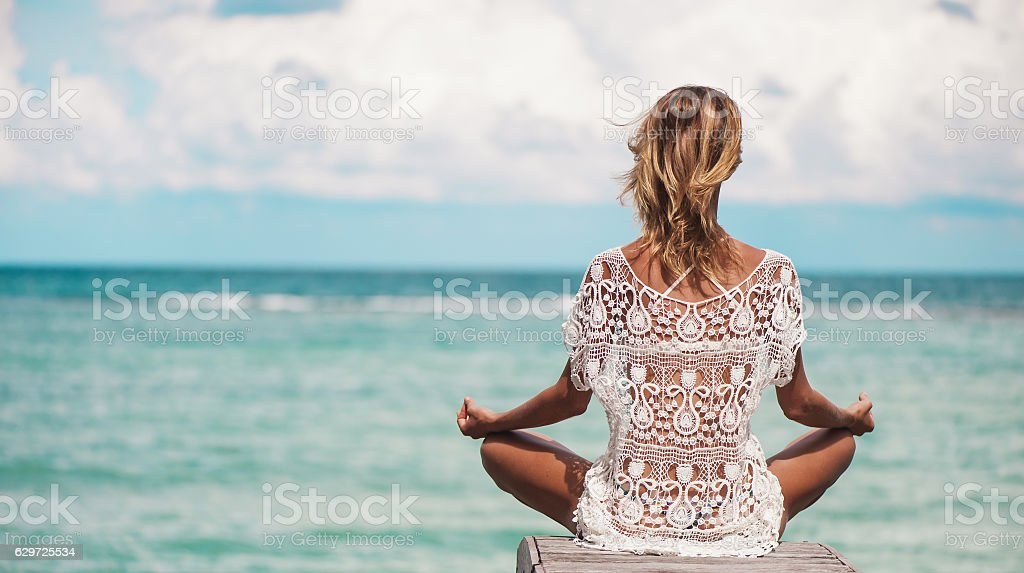 young woman meditation at the beach stock photo
