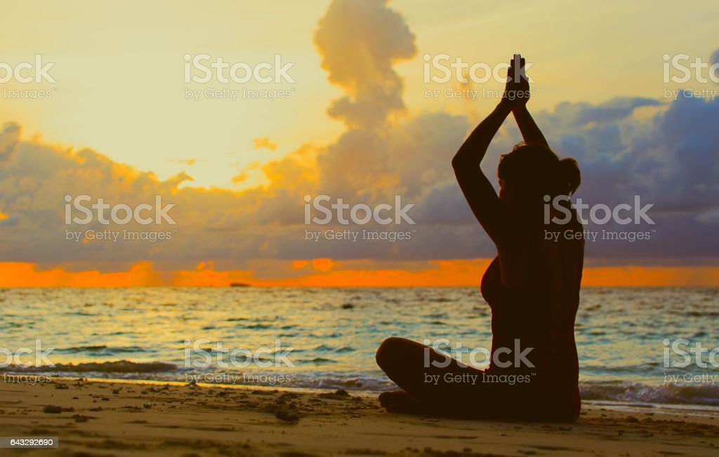 young woman meditation on sunset beach stock photo