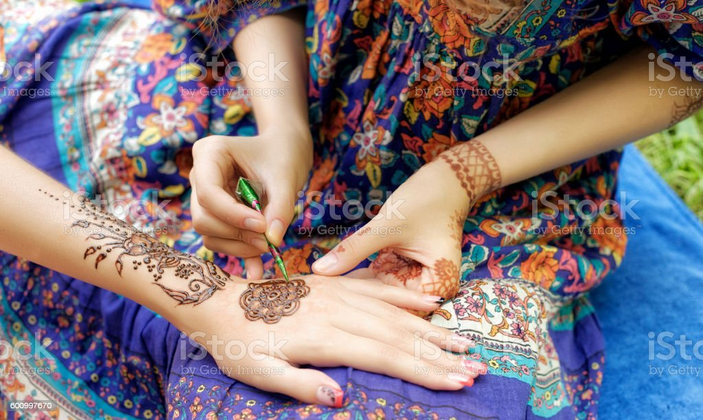 young woman mehendi artist painting henna on the hand stock photo