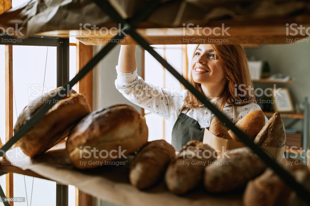 Young woman merchandise bread in shop stock photo