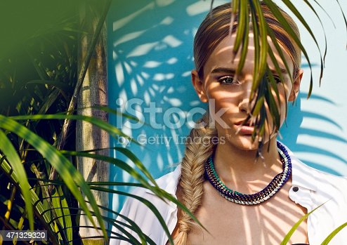 Close up of beautiful fashion model in the jungle scene, thinking while her eager eyes searches for the ray of sun, shadows falling on her face creating a warm lively atmosphere. Fresh breeze slightly bearing her white blouse making her feel strong and powerful.