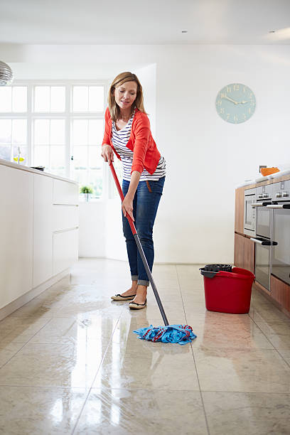 Young woman mopping kitchen floor Middle Aged Woman Mopping Kitchen Floor mop stock pictures, royalty-free photos & images