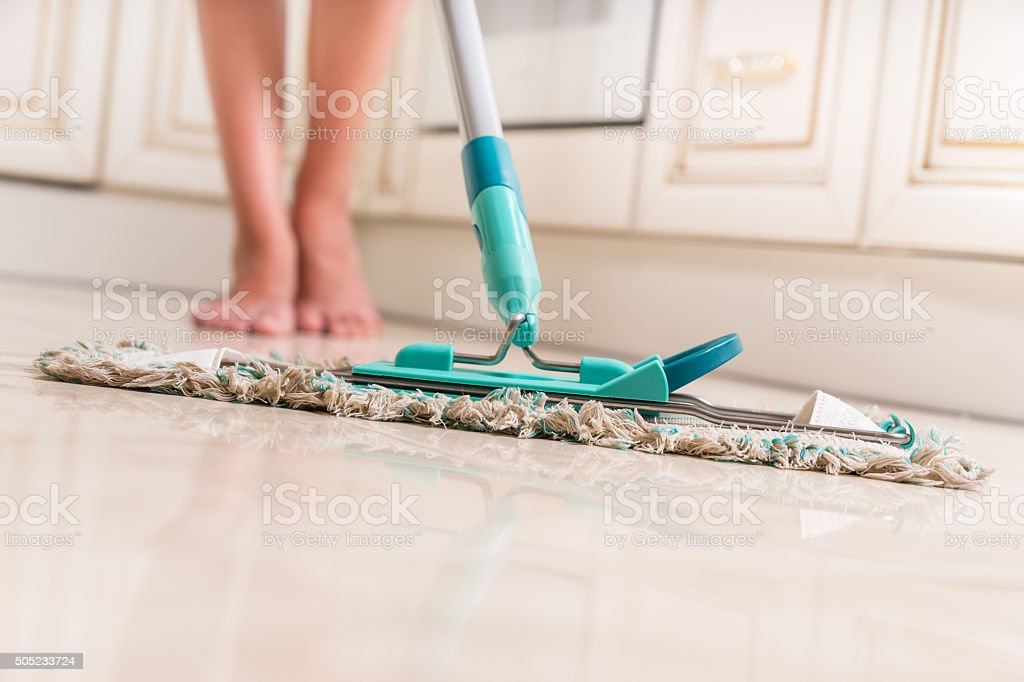 Young Woman Mopping Kitchen Floor stock photo