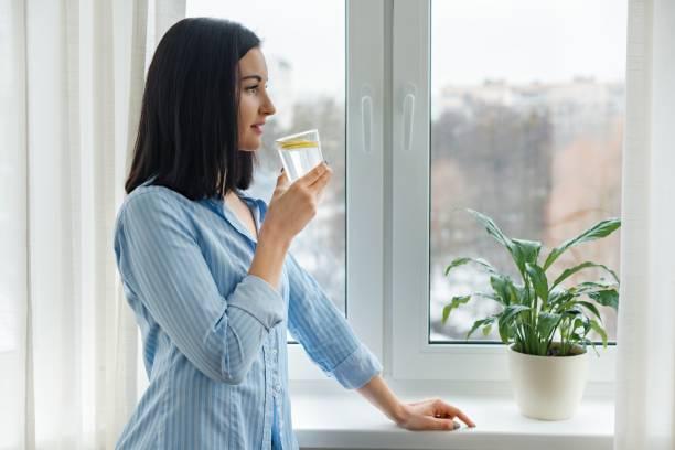 Mujer joven mañana en su casa cerca de la ventana de agua con limón, vitamina tomar invierno primavera temporada - foto de stock